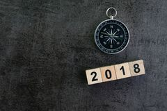 Compass and wooden block number 2018 on dark black background as. Year 2018 prediction or direction concept Stock Images