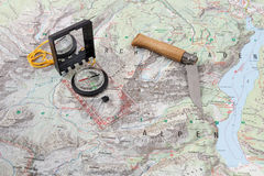 Compass and wooden-handled knife on a hiking map Royalty Free Stock Photos