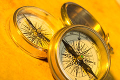 Compasses. Three old style gold compasses on yellow paper Stock Image