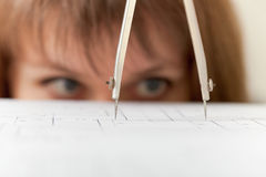 Compasses and drawing close up on face background. Compasses and the drawing close up on a face background Stock Image