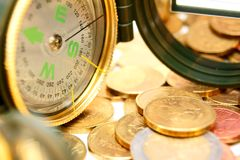 Compasses and gold coins. Royalty Free Stock Image