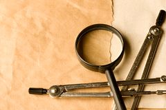 Compasses and magnifying glass Stock Images