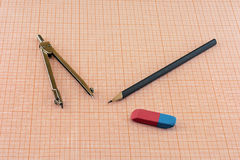 Compasses, pencil and eraser lying on a sheet of graph paper Stock Images