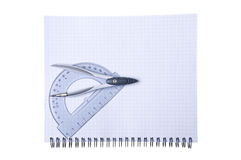 Compasses and protractor on copybook Royalty Free Stock Image