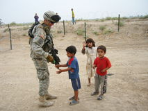 Compassion of a soldier. A 10th Mountain Soldier pauses on patrol to offer local children gum in Iraq stock image