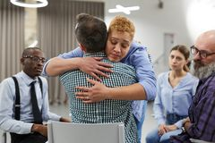 Compassion in Support Group. Portrait of mixed race women hugging psychologist during therapy session in support group, copy space royalty free stock photography