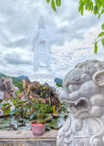 Compassion and wicked. In Da Nang, Vietnam, July 13, 2015: Statue of the sound standing Buddha symbolizes the Buddhist concept of good beside the lion symbolizes Royalty Free Stock Image
