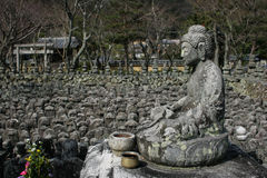 The Compassionate Buddha. A stone statue of Buddha with hundreds of stones representing the bodies of poor people who died with no graves. This is at Adashino stock photography