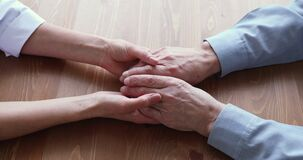 Compassionate young doctor giving psychological geriatric help to retired patient.