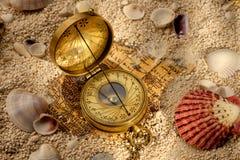 Compasso antigo na areia com conchas do mar Imagens de Stock Royalty Free