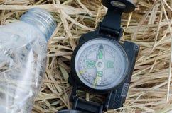 Compasso com a garrafa de água no feno Imagem de Stock Royalty Free