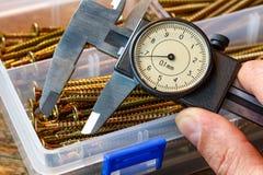 Compasso de calibre de corrediça com a escala redonda na mão do homem Imagens de Stock Royalty Free