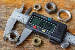 Compasso de calibre eletrônico de Digitas com as porcas usadas na tabela de madeira na oficina foto de stock
