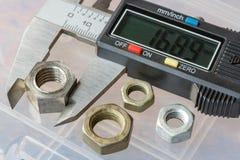 Compasso de calibre eletrônico de Digitas com porcas usadas em um fundo da caixa de armazenamento imagens de stock