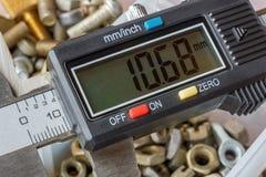 Compasso de calibre eletrônico de Digitas em um fundo da caixa de armazenamento aberta com parafusos usados e o close up nuts imagem de stock royalty free