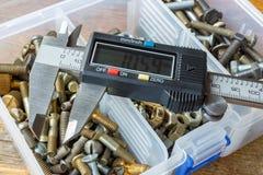 Compasso de calibre eletrônico de Digitas na caixa de armazenamento com parafusos e porcas na tabela de madeira na oficina fotografia de stock