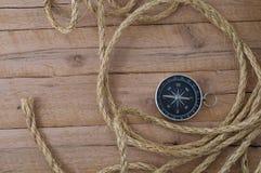 Compasso e corda náutica nas pranchas de madeira Foto de Stock
