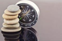 Compasso e uma pilha de seixos do mar Fotos de Stock Royalty Free