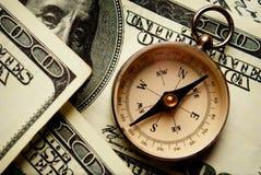 Compasso magnético em notas do dólar americano Imagens de Stock
