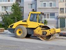 Compattatore giallo dell'asfalto di combinazione al sito del sito della costruzione di strade vicino all'edificio residenziale fotografia stock