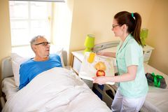 Compele a favor at nursing home. Nurse brings fresh food for senior man stock photo