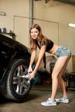 Compelling female repairs the front wheel with pneumatic key. Compelling brunette repairs the front wheel with a pneumatic key. Looks at the camera with a sweet Royalty Free Stock Image