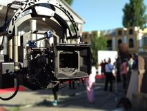 Compendium with cinema camera on flying head. Flying camera stopped after shooting on stage with urban background. Front side of stock photo
