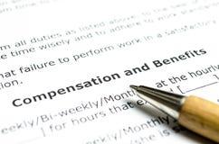 Compensazione e benefici con la penna di legno fotografia stock