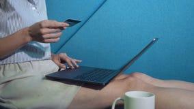 Compera della giovane donna online con la carta di credito sul computer portatile video d archivio