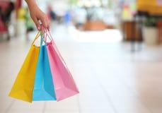Compera! Mano femminile che tiene i sacchetti della spesa variopinti Immagini Stock Libere da Diritti
