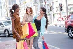 Comperando con gli amici shopaholic Tre tengono i sacchetti della spesa in Th Fotografia Stock