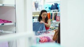 Comperando nel deposito, comperante dipartimento dell'abbigliamento del ` s dei bambini la giovane donna, madre sceglie le cose p stock footage