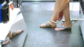 Comperando nel deposito, comperante primo piano, piede femminile in sandali in un negozio di scarpe, la donna prova sopra i bei s stock footage