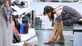 Comperando nel deposito, comperante in un negozio di scarpe, una ragazza, donna che si siede sul sofà, prova sopra i bei sandali  stock footage