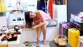 Comperando nel deposito, comperante in un negozio di scarpe, una ragazza, donna che si siede sul sofà, prova sopra i bei sandali  video d archivio