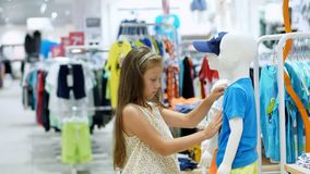 Comperando nel deposito dipartimento dell'abbigliamento del ` s dei bambini la ragazza, bambino, sceglie le cose nel deposito Pic stock footage