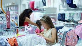 Comperando nel deposito dipartimento dell'abbigliamento del ` s dei bambini la ragazza, bambino, sceglie le cose nel deposito Pic archivi video