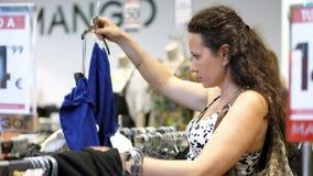 Comperando nel deposito, la giovane donna, sceglie le cose, si veste per se stessa video d archivio