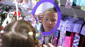 Comperando nel deposito, la ragazza, bambino, sceglie le forcelle, gli elastici, banda dei capelli, nel deposito provando sulle f stock footage