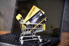 Comperando online con la carta di credito in carrello sui precedenti del computer portatile per il concetto online di pagamento a fotografia stock