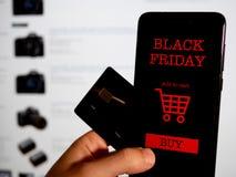 Comperando online per venerdì nero sul telefono e sulla carta di credito Concetto immagini stock