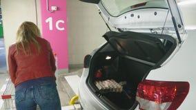 Comperando, una donna mette le borse dal carretto per la compera nel tronco dell'automobile parcheggio sotterraneo del supermerca video d archivio
