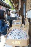 Comperi dentro il santuario shintoista ed il tempio buddista nel Giappone che vende Omikuji o le strisce di carta con le fortune  Fotografie Stock Libere da Diritti