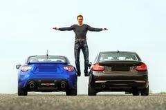 Comperison de dos coches deportivos en manera de raza imagen de archivo