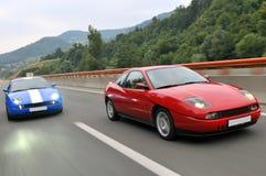 Competência de carros de ajustamento abaixo da estrada Foto de Stock