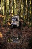 Competência em carros fora de estrada Carro offroad sujo com a floresta da queda no fundo Imagens de Stock Royalty Free