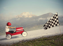 Compete with children car. Child climb a mountain with a small car to get to the flag Royalty Free Stock Photo