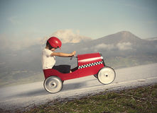 Compete with children car. Child climb a mountain with a small toy car Stock Images