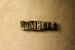 COMPETE - o close-up vintage sujo da palavra typeset no contexto do metal Fotografia de Stock Royalty Free