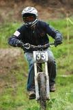 Competencia en declive extrema de la bici de montaña bajo la lluvia Foto de archivo libre de regalías